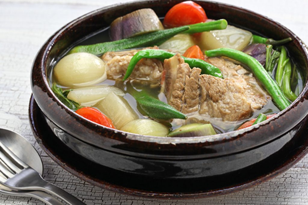Put the freshly cleaned pot back (into the instant pot), and place the parboiled pork in the inner pot, add tomatoes, sliced white radish, taro (or potatoes), onion, and fish sauce. Pour the chicken stock (if using) or water.